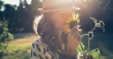 Mulher cheirando uma flor de girassol em um jardim