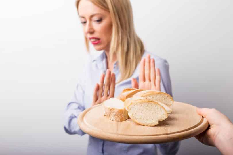 Mulher com as duas mãos em frente ao seu corpo e a uma bandeja com pão.