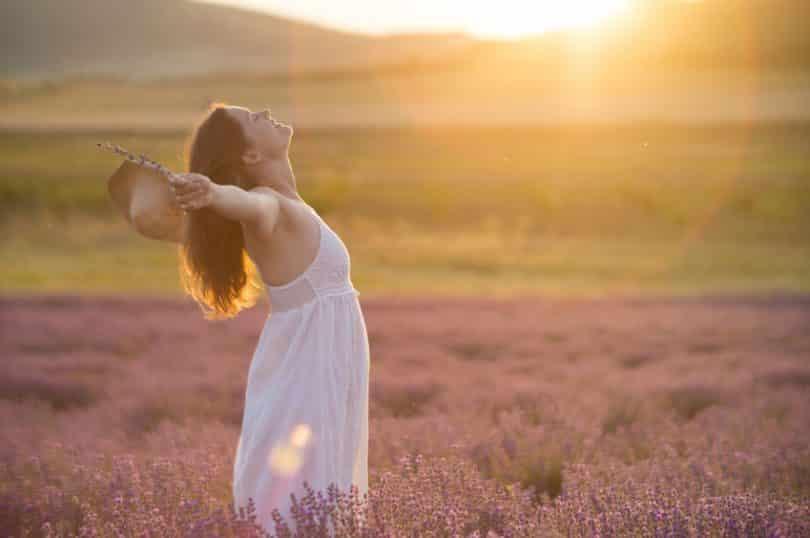 Mulher de perfil com braços abertos em campo com sol refletindo
