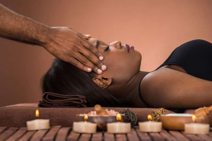 Mulher deitada de olhos fechados com pessoa aplicando a shiatsuterapia