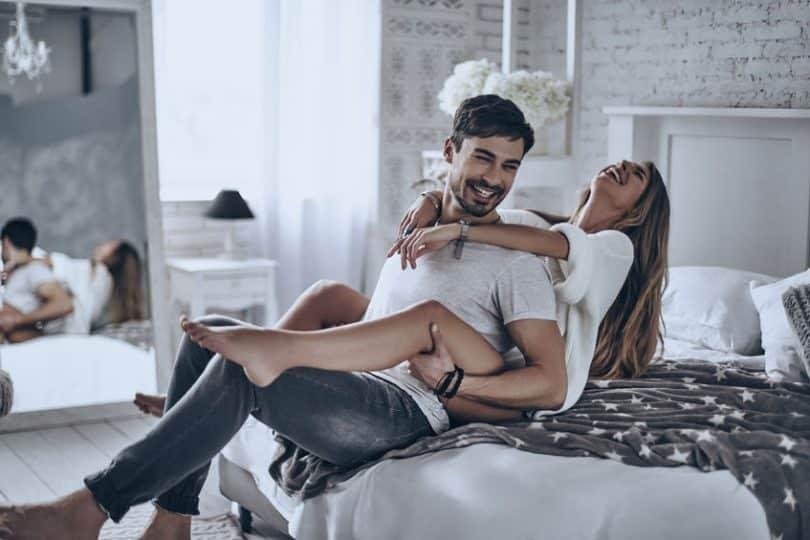 Casal feliz com homem sentado na cama e mulher atrás ambos sorrindo