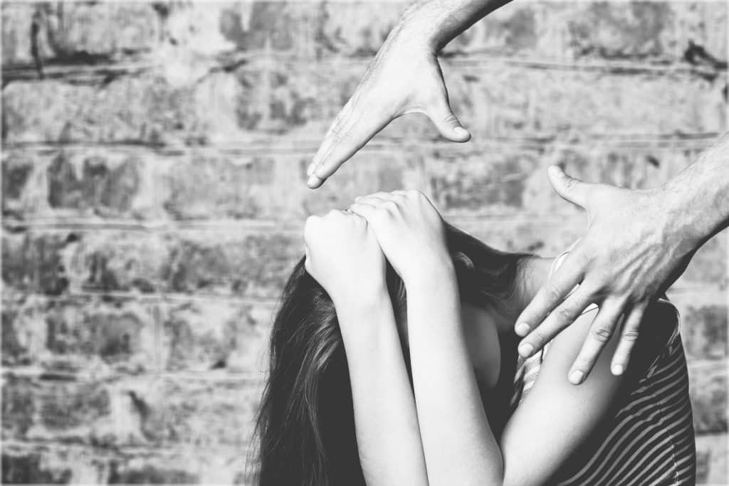 Imagem de uma mulher sentada com os braços protegendo o seu rosto e sobre a cabela dela as mãos de um homem querendo cometer um ato de violência.