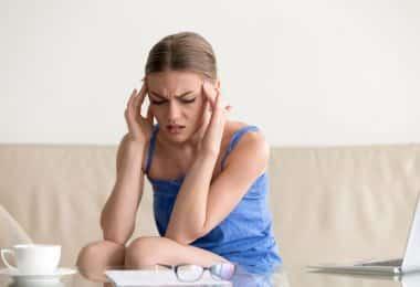 Mulher com mãos na cabeça e expressão de cansaço