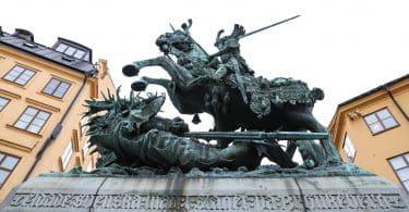 Estátua gigante de São Jorge em um cavalo, segurando sua espada, com um dragão morto embaixo.