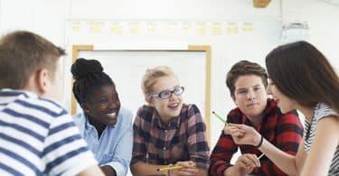 Grupo de alunos sentados ao redor de uma mesa, conversando.