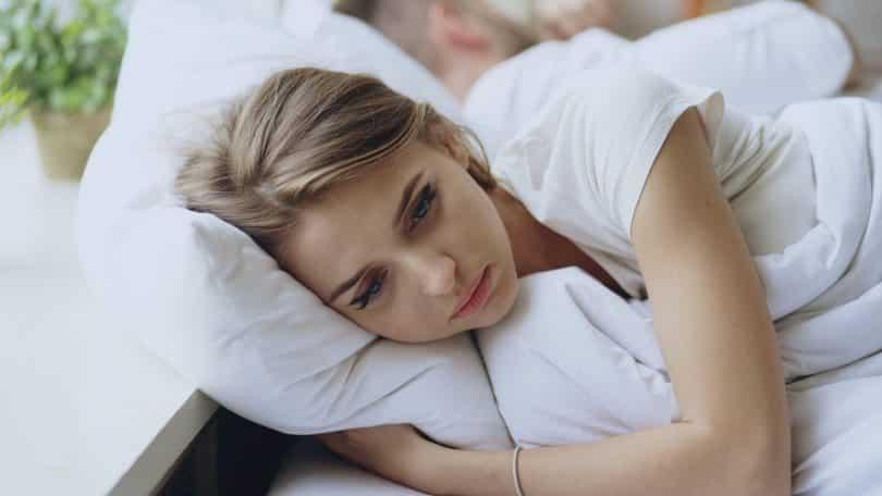 Mulher deitada na cama, com olheiras e aparência cansada.