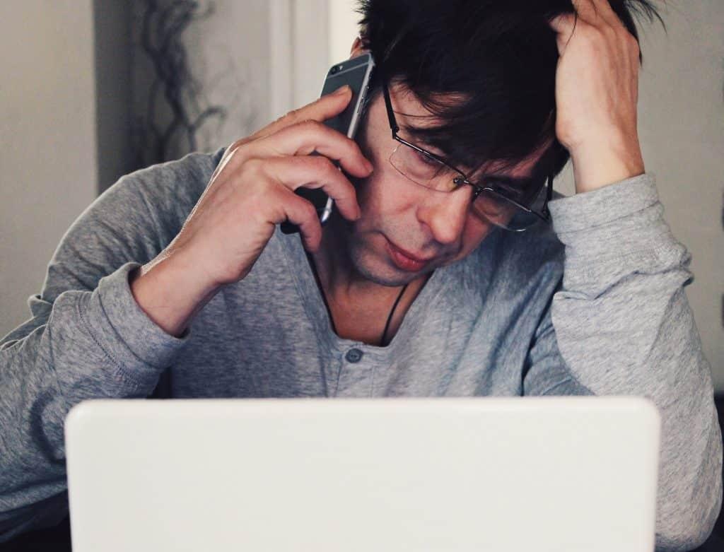 Homem em frente a um computador, com a cabeça apoiada em uma mão, e segurando o celular com a outra.