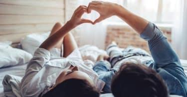Casal deitado na cama fazendo coração com as mãos