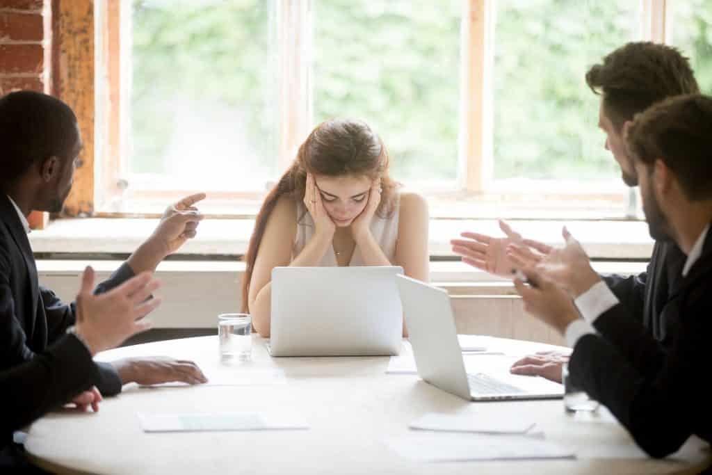 Homens discutindo com uma mulher, que segura a cabeça com as mãos, em uma mesa de reunião de esritório.