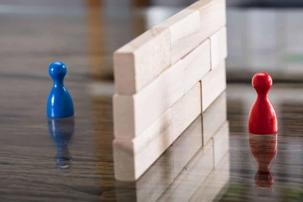 Duas peças de jogo de tabuleiro, representando pessoas, separadas por um pequeno muro de madeira.