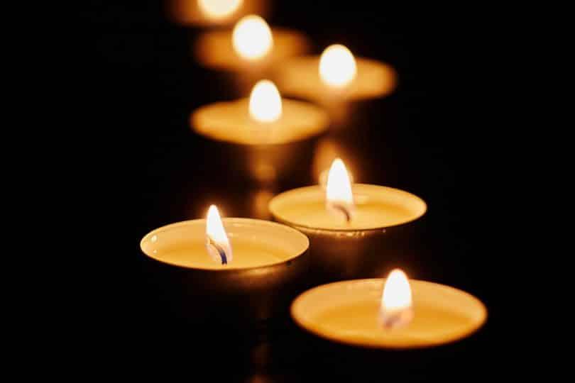 Pequenas velas acesas em uma fileira.