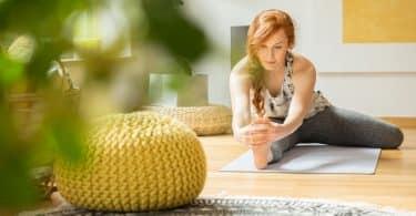 Mulher praticando yoga em um tapete, na sala de casa.