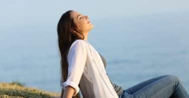 Mulher sentada na beira de um rio, com a cabeça voltada pra cima, sorrindo.