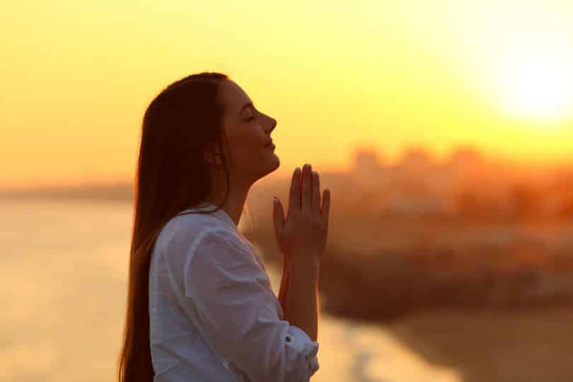 Mulher com mãos em frente ao corpo unidas e pôr-do-sol ao fundo