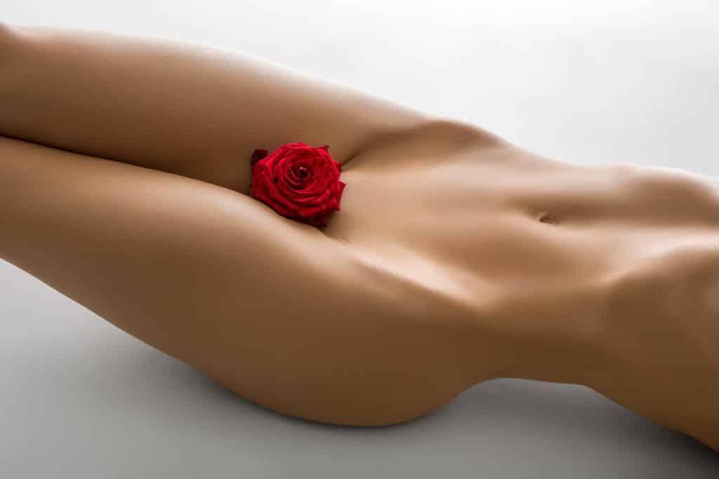 Imagem nú do orpo de uma mulher - do pescoço para baixo. Ela está com um botão de rosa vermelha entre as pernas, próximo à sua região sexual.
