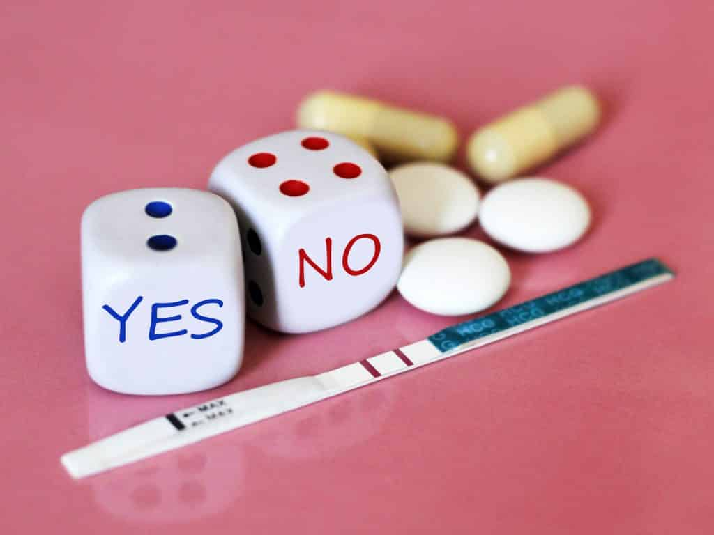 imagens de teste de gravidez positivo. Ao lado dele dois dados onde estão escritas as palavras YES e NO. Ao lado alguns comprimidos.