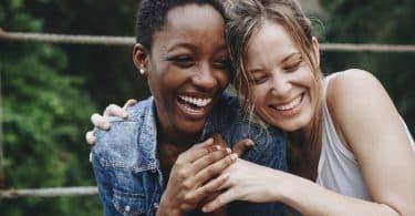 Duas mulheres abraçadas sorrindo