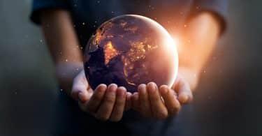 Mãos segurando uma miniatura do planeta Terra iluminada.