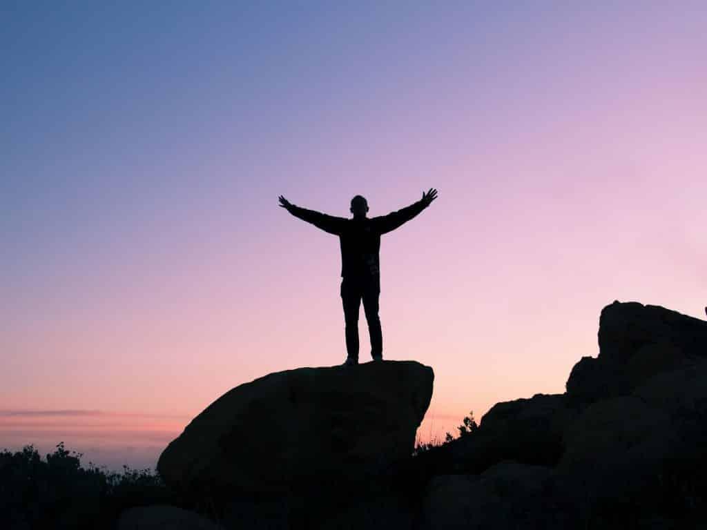 Silhueta de uma pessoa com os braços abertos sobre uma pedra, ao pôr do sol.