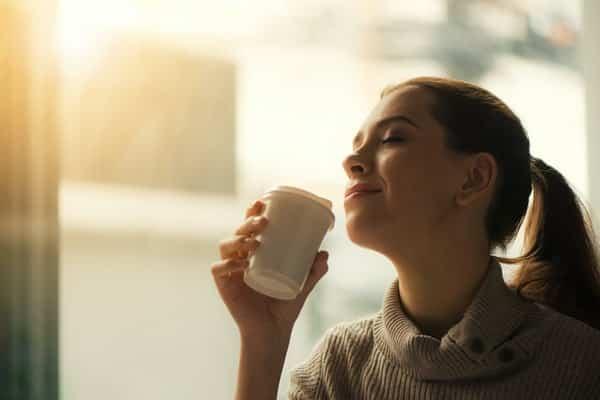 Mulher tomando café de olhos fechados e sol refletindo