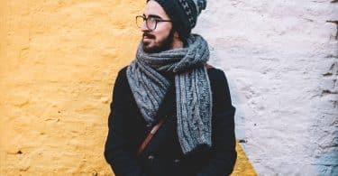 Homem usando roupas de frio em frente a uma parede.