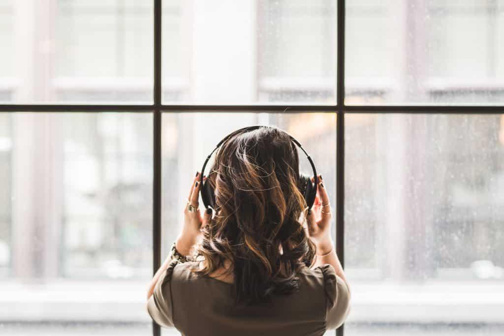 Mulher vista de costas olhando pela janela enquanto escuta música em seu fone de ouvido.