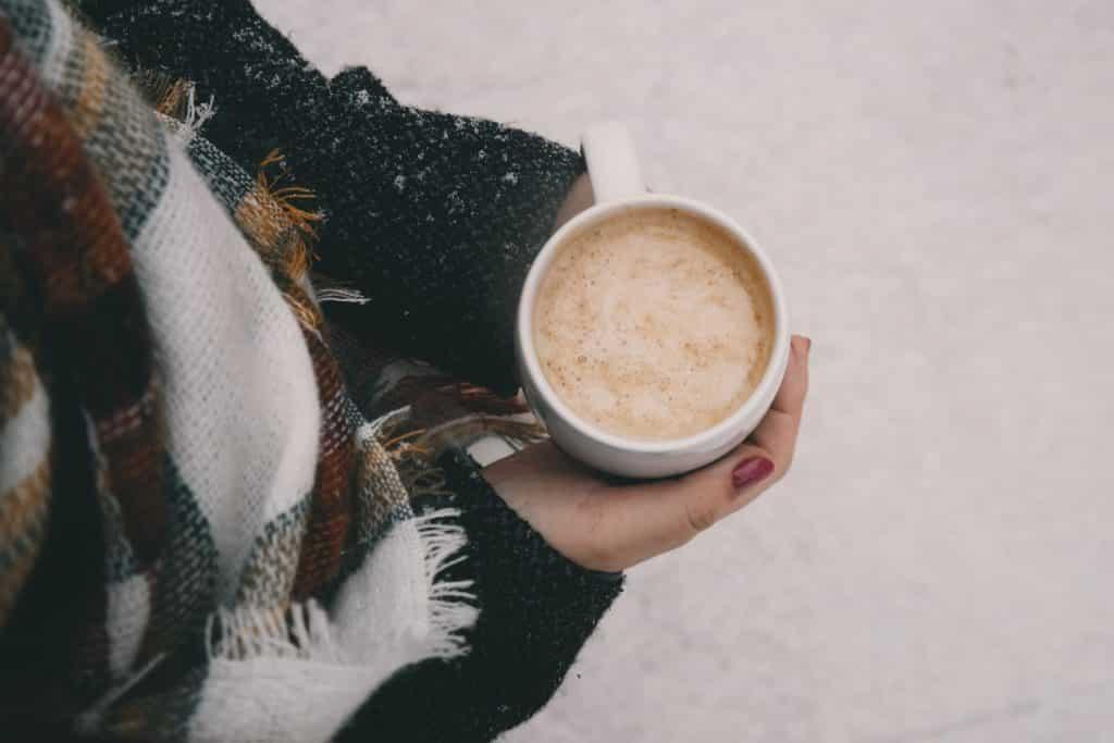 Pessoa com roupas de frio segurando uma xícara de café quente.