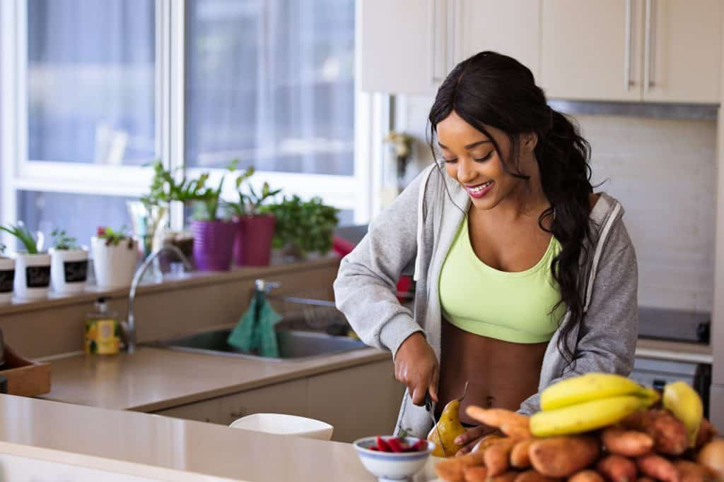 Mulher sorri enquanto corta frutas em sua cozinha.