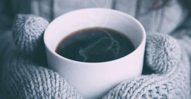 Pessoa usando luvas segurando xícara de café