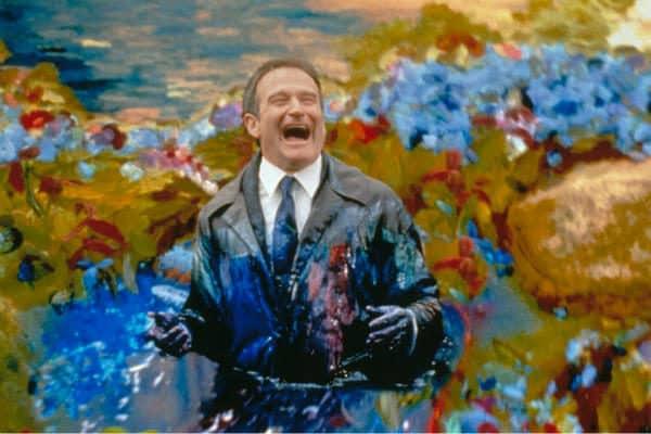 Homem com tinta em sua roupa e sorrindo
