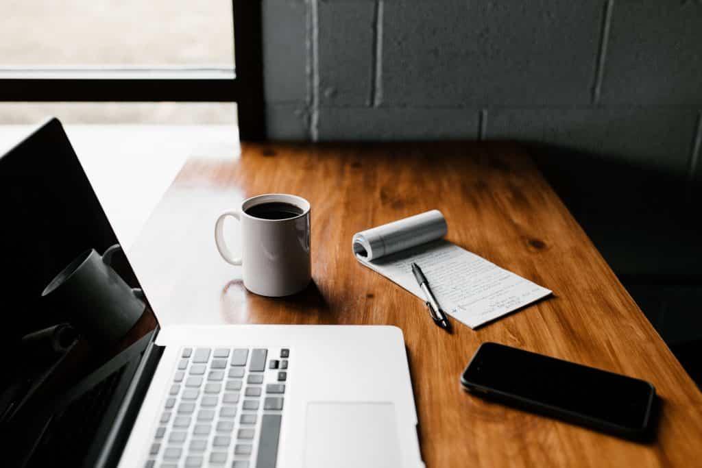 Mesa com notebook aberto e ao lado uma xícara de café junto com caderno de anotação