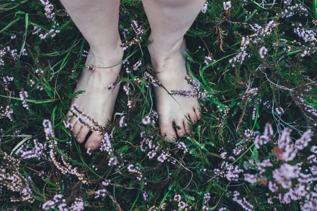 Mulher com os pés descalços em um gramado com flores