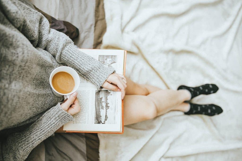 Mulher sentada na cama com livro aberto apoiado em suas pernas e segurando xícara de chá