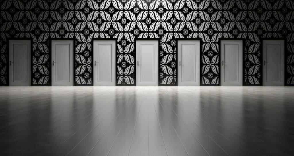 Sete portas idênticas, lado a lado, em uma parede, indicando a necessidade de uma escolha.