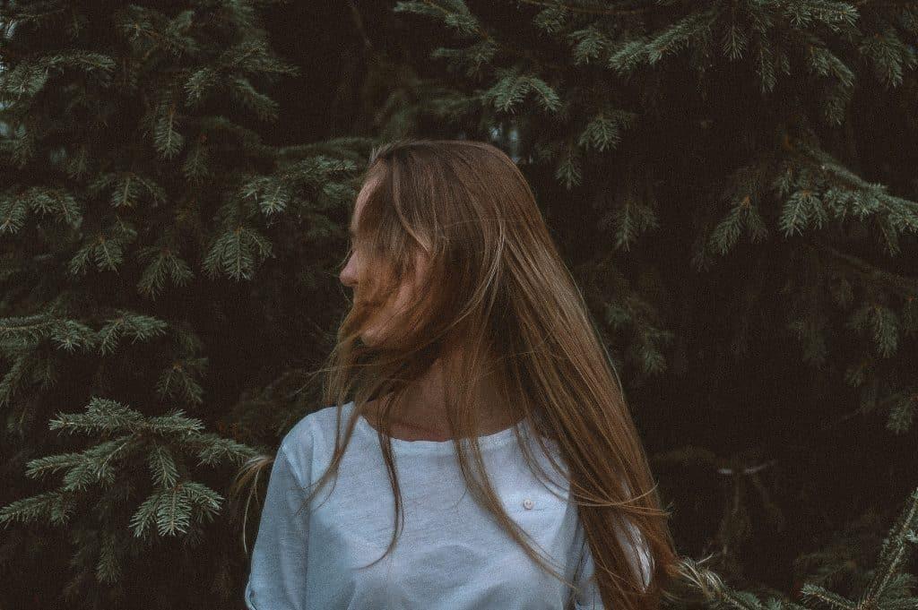Mulher com rosto de lado e cabelos no rosto em um jardim
