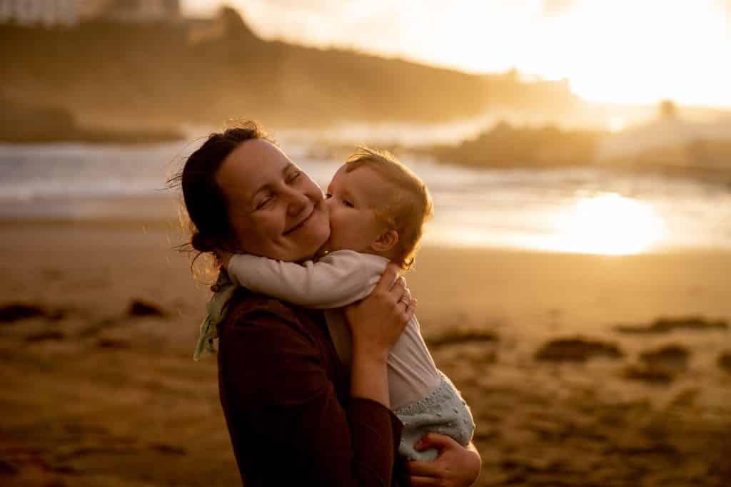 Bebê beijando sua mãe na bochecha na praia.