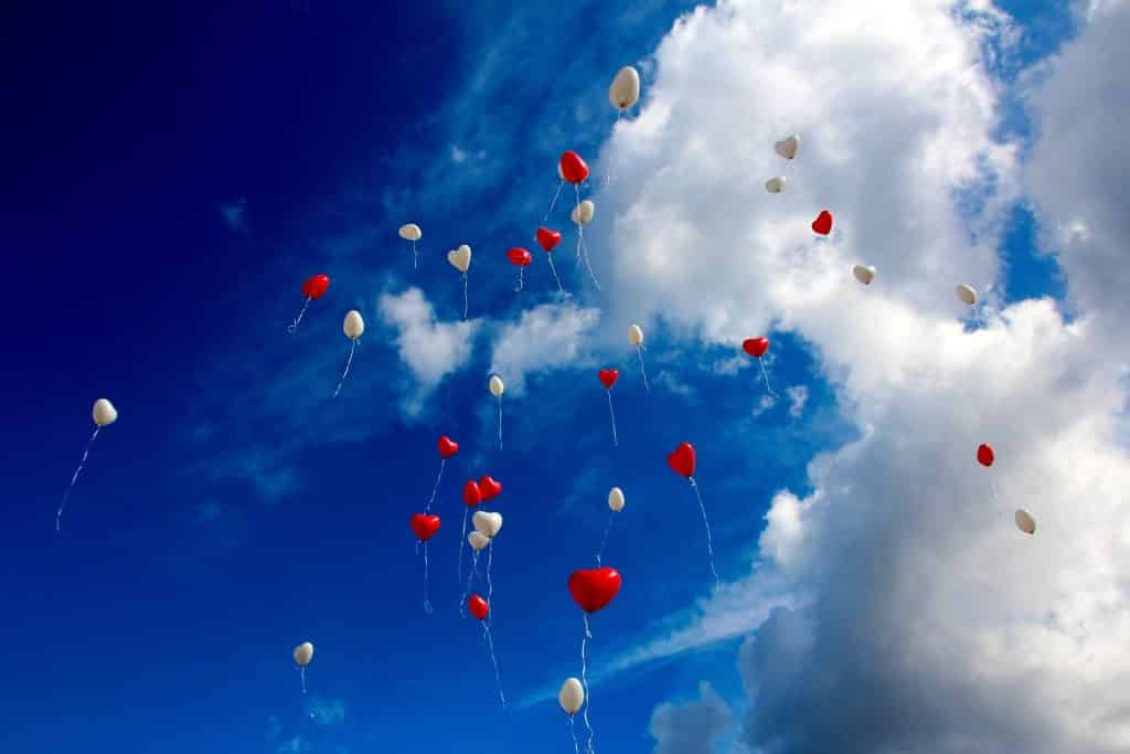 Imagem do céu azul e com poucas nuvens representando a reciprocidade. Vários balões em formato de coração nas cores vermelho e branco estão soltos no céu.