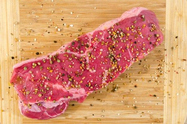 Pedaço de carne temperado visto de cima em tábua de madeira