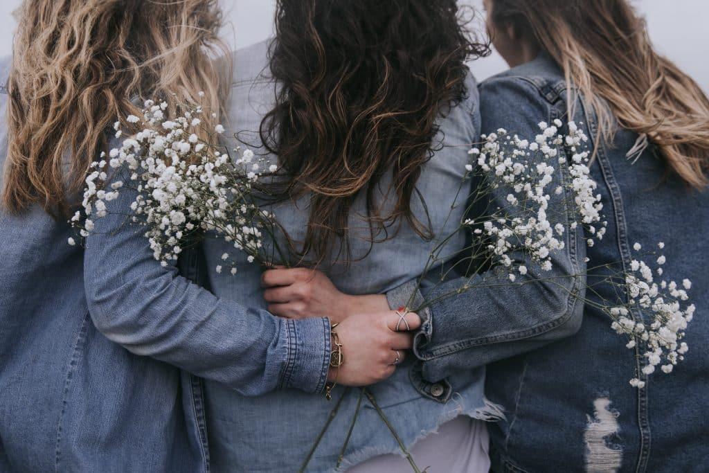 Mulheres abraçadas segurando flor
