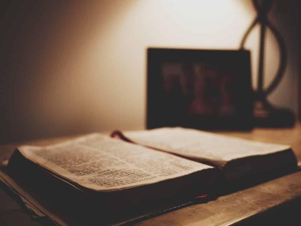 Imagem da bíblia, o livro sagrado da espiritualidade. Ele está aberto sobre uma mesa de madeira.