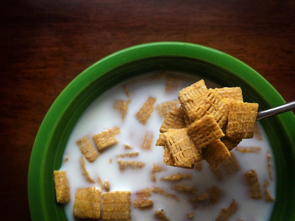 Imagem de um bowl na cor verde e dentro dele cereais com leite.