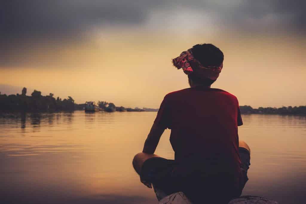 Imagem de um final de tarde em frente ao um grande rio. Na beira dele está um jovem garoto triste e solitário. Parece que está depressivo.