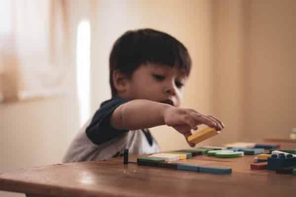 Menino brincando com peças coloridas em cima da mesa