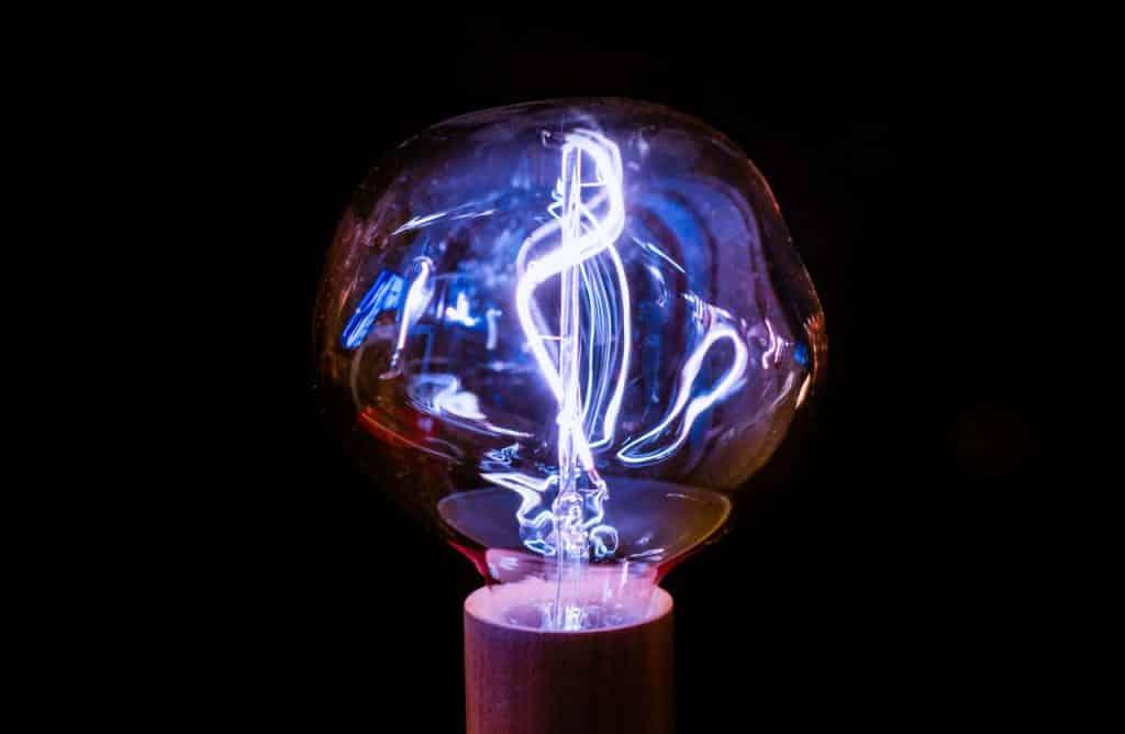 Lâmpada redonda entortada, com luz neon dentro.
