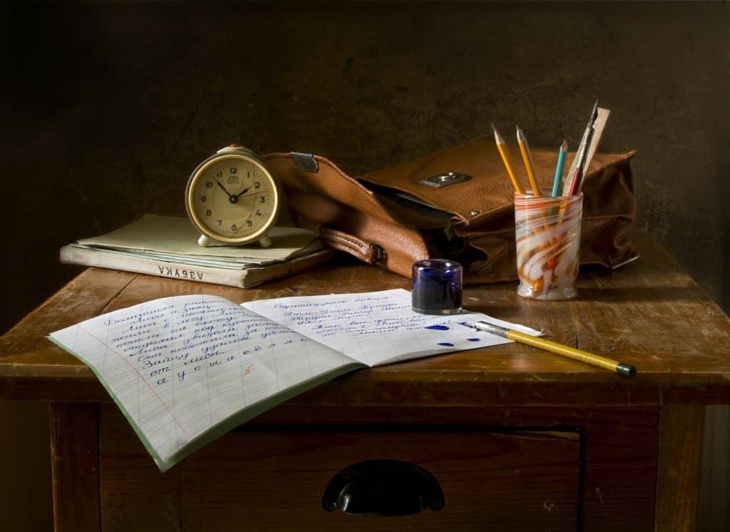 Escrivaninha de madeira com cadernos, lápis, uma bolsa e um relógio em cima.