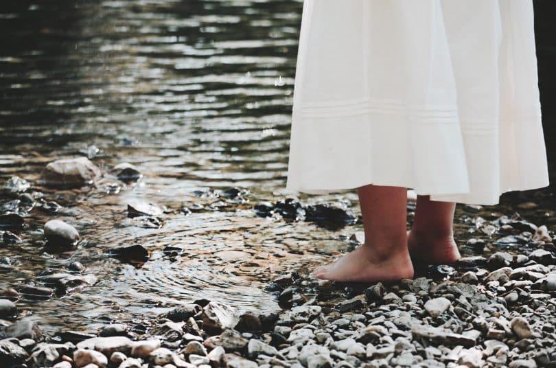 Mulher com seus pés descalços em pedras ao lado de um rio