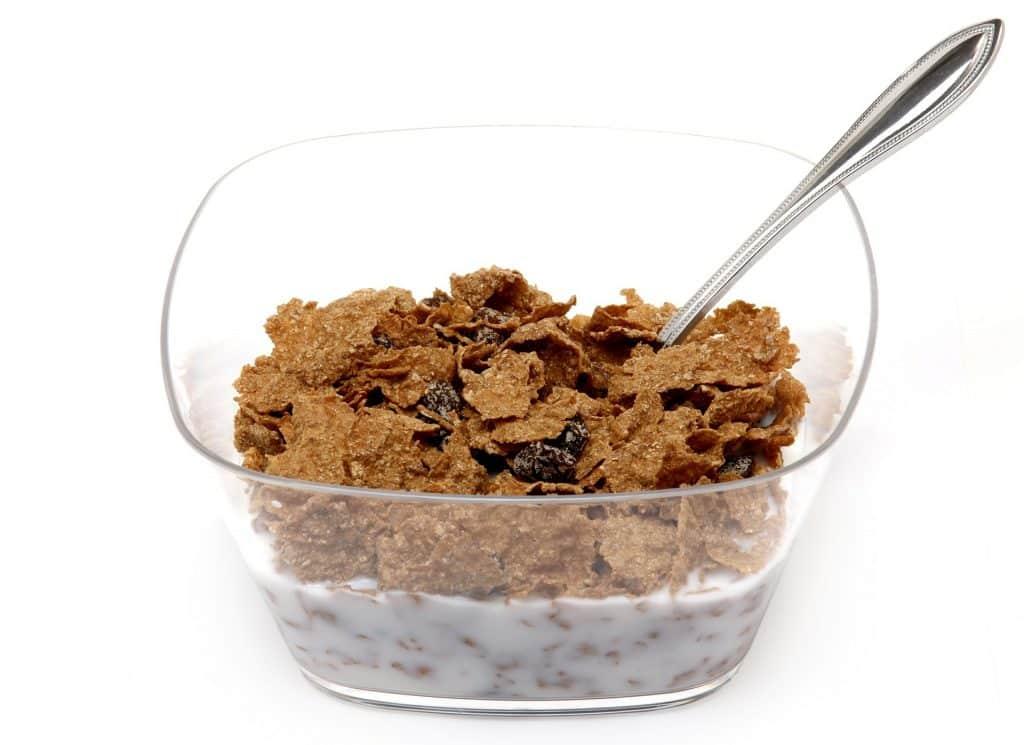Imagem de um pote de vidro com cereais, leite e uva passa.