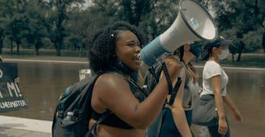 Mulher falando em um megafone em protesto