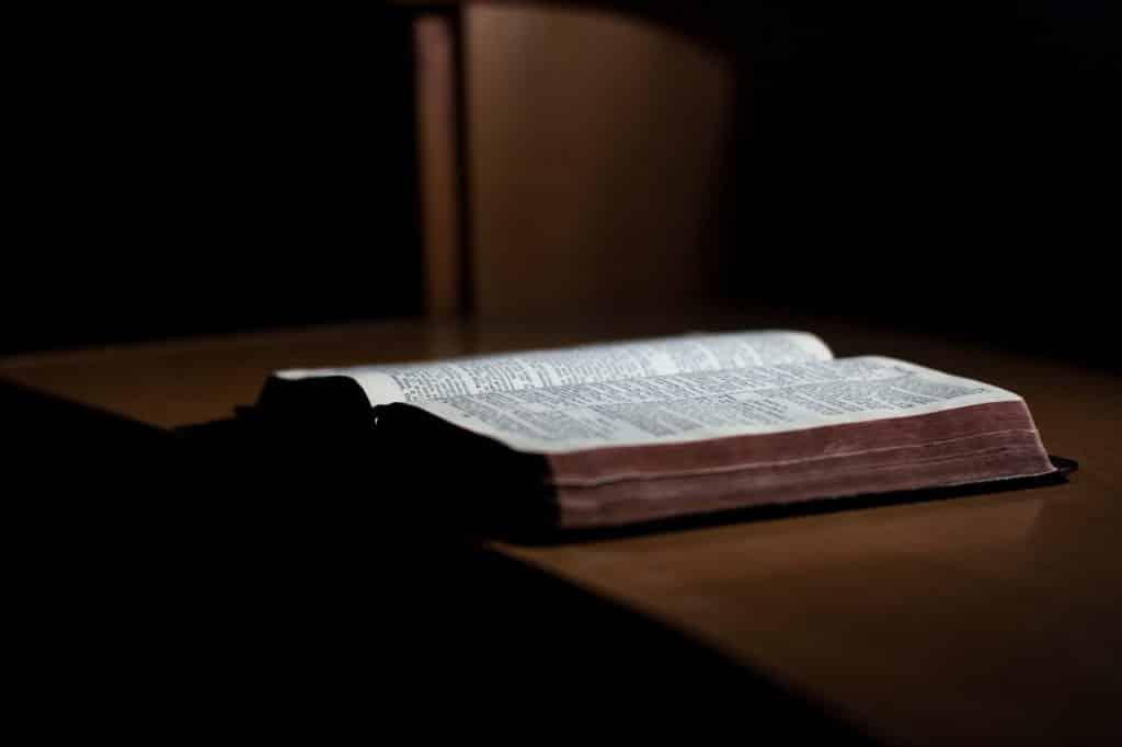 Bíblia aberta em cima de móvel de madeira.