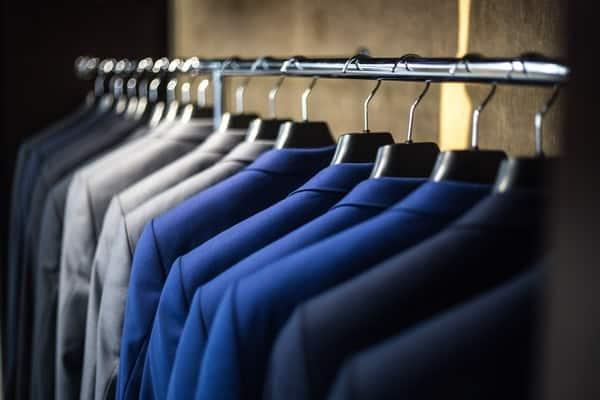 Cabides com roupas organizadas por tons de cor